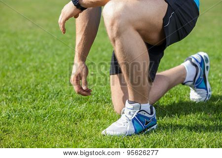 Young healthy athlete has his shoelaces untied