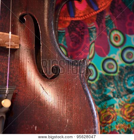 Antique Violin Closeup Against Colorful Print