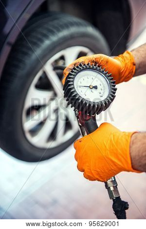 Car Mechanic Checking Tyre Pressure