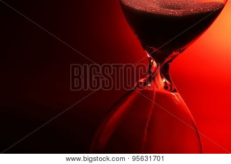 Hourglass on dark red background