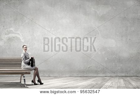 Young businesswoman with suitcase sitting on bench