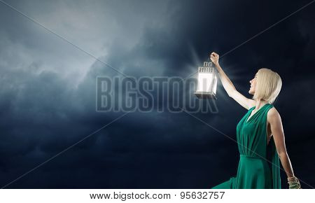 Young attractive woman in green dress with lantern walking in darkness