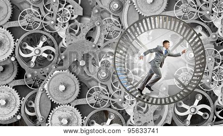 Young businessman running in wheel of gears mechanism