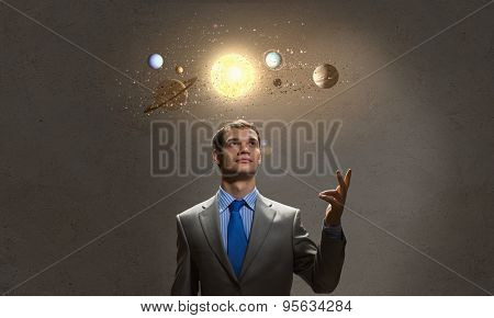 Young businessman and planets of sun system