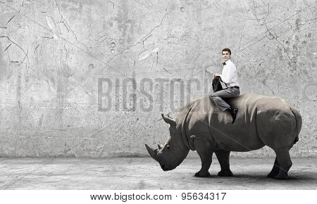 Young handsome fearless man riding huge rhino