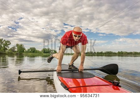 senior male paddler starting his workout on a  stand up paddleboard -  a local lake in Colorado under cloudy sky