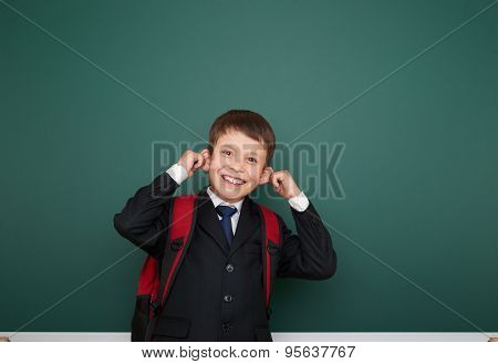 Schoolboy with backpack on school board background