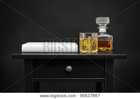 a book, and a bottle and a lowball glass with liquor on a black table, over a black background