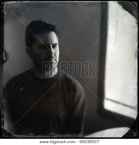 Instagram filtered portrait of a depressed man sitting by a window