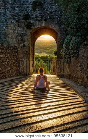 Girl sitting relaxed in the light of setting sun through the medieval castle wall arch