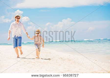 Father with son running barefoot on the sea surf line having great holidays time