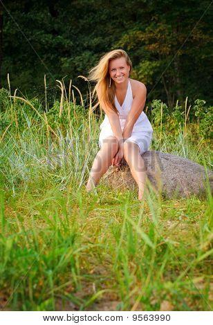 Pretty Woman Sitting On Big Stone