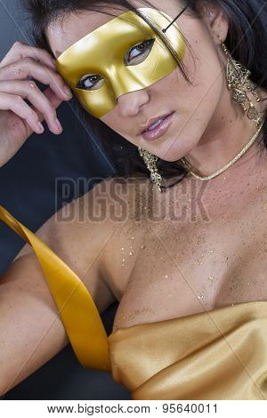 A brunette model poses with a mask in a studio environment.