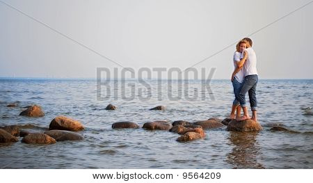 Couple Embrace On A Stone In Sea