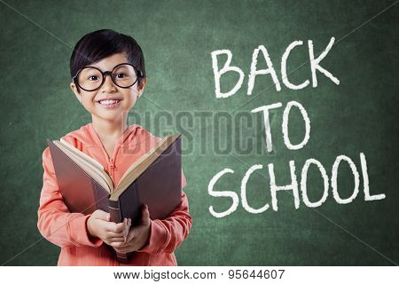 Cute Girl Back To School And Holds Book In Class
