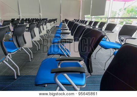 Many Blue Chairs Arranged Neatly In A Training Room.