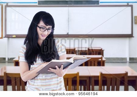 Student Standing In Class While Reading Book