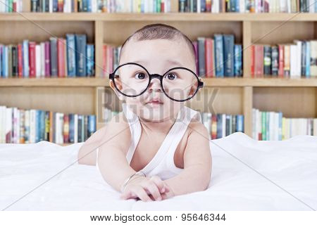 Sweet Baby With Glasses And A Bookcase Background