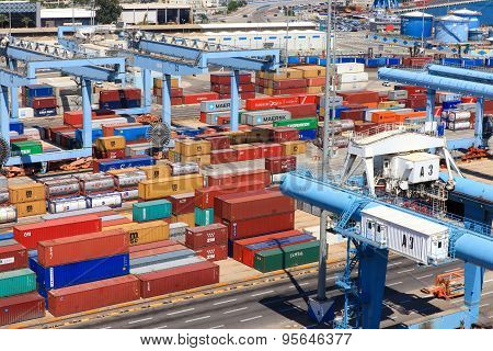 Various brands and colors of shipping containers stacked in a holding platform waiting for loading