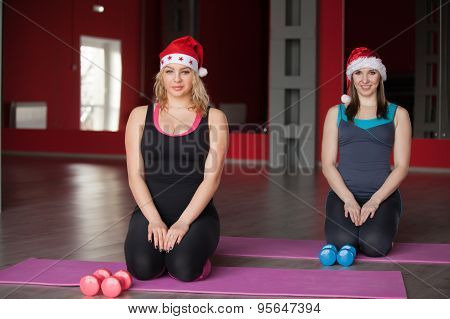 Two Pretty Girls In Santa Claus Hats Sit On Mats In Fitness Center
