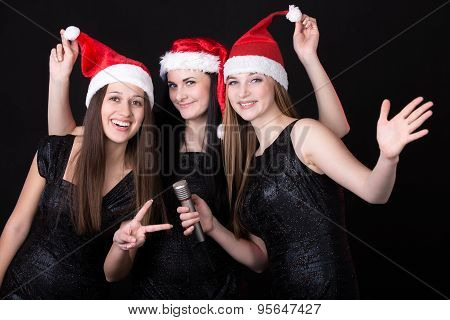 Three Attractive Young Santa Girls With Microphone