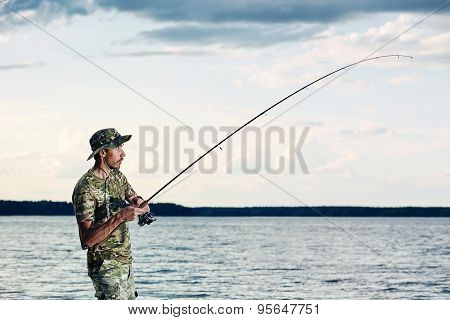 Surprised Man Caught A Fish On The Lake  During His Vacation