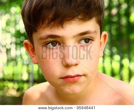 preteen handsome boy close up portrait on summer green background