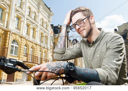 Attractive young man is cycling across city