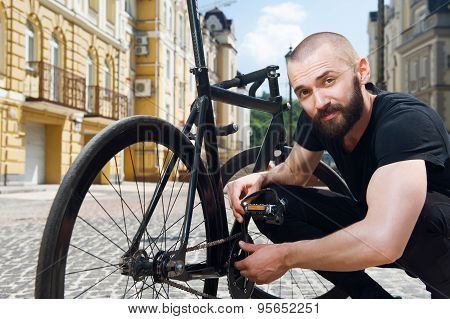 Attractive hipster men is correcting his transport in city