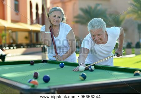 old couple on vacation playing billiards