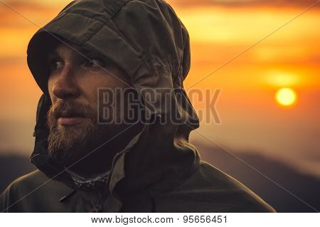 Man Traveler bearded face alone outdoor with sunset mountains