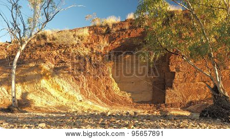 Upwards Ochre lines in the banks of a creek at sunset