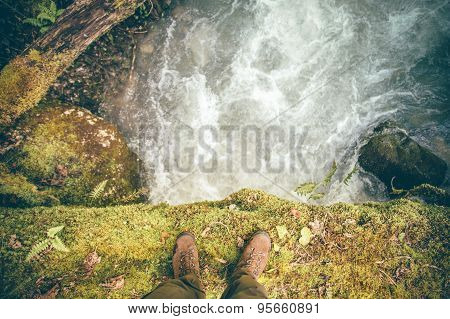 Feet Man trekking boots hiking outdoor with river and stones on background
