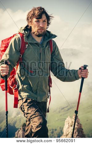 Young Man bearded with backpack and trekking poles relaxing outdoor