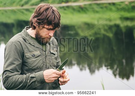 Young Man Fisherman bearded standing with knife and rod