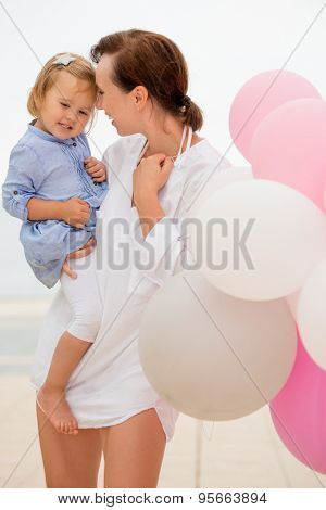 Happy young mother with her small daughter in her arms nuzzling her forehead with her face in a laughing fun gesture as they stand outside with pink and white party balloons.