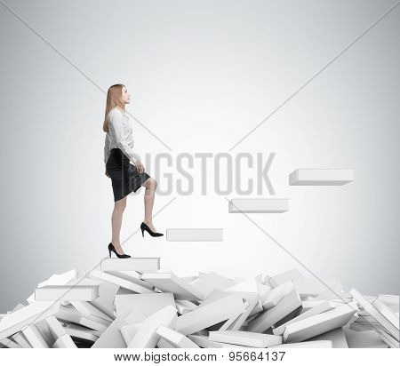 Young Business Woman Is Going Up To The Stairs. A Concept Of Education Process. White Book On The F