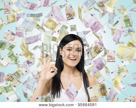 Brunette Woman Shows Ok Sign. Euro Notes Are Falling Down Over Blue Background.