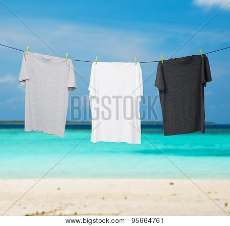 Close Up Of A Dark Grey, White And Grey T-shirts On The Rope. Tropical Sand Beach And Ocean As Backg