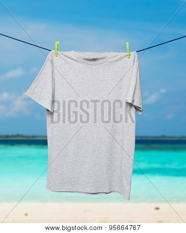 Close Up Of A Grey T-shirt On The Rope. Tropical Sand Beach And Ocean As Background.