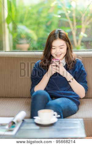 Trendy And Beautiful Young Woman Typing On A Smartphone