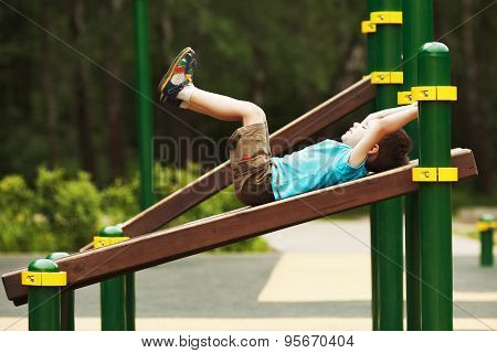 Little Boy Exercise On The Playground
