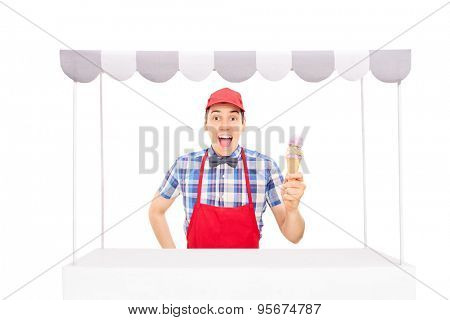 Excited young vendor with a red cap and apron holding an ice cream cone behind an ice cream stand isolated on white background