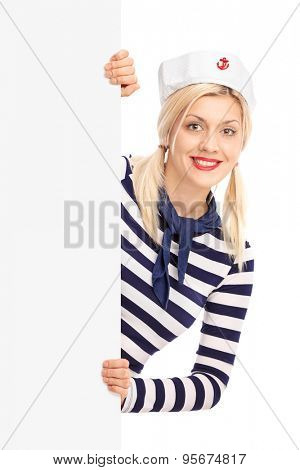 Vertical shot of a young female sailor standing behind a blank signboard and looking at the camera isolated on white background