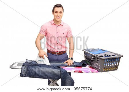 Cheerful young man ironing a pair of jeans on an ironing board and looking at the camera isolated on white background