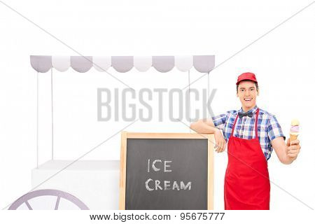 Young male vendor standing by an ice cream stand and holding an ice cream cone isolated on white background
