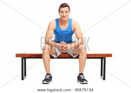 Young sportsman sitting on a wooden bench and looking at the camera isolated on white background