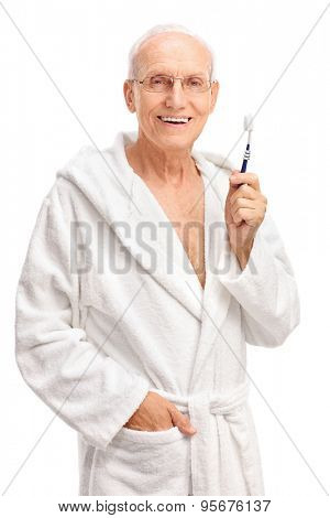 Vertical shot of a cheerful senior in a bathrobe holding a toothbrush and looking at the camera isolated on white background