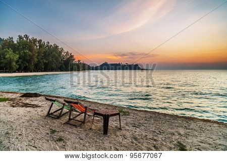 Beach chairs set in the sand overlooking sea sunset. Thailand