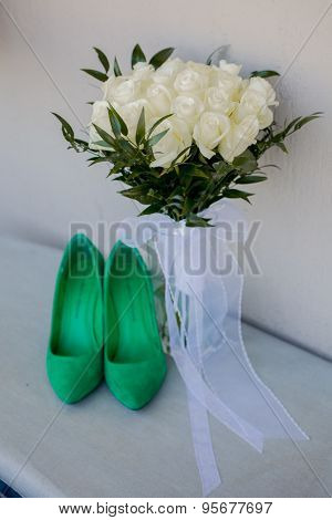 Green wedding shoes and bridal bouquet of white roses